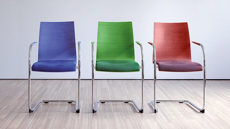 Drei farbige Stühle stehen nebeneinander.