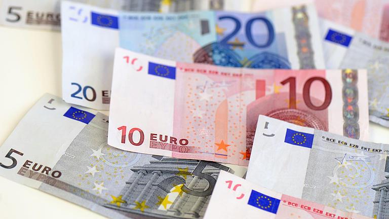 Auf einer hellen Oberfläche liegen verschiedene Geldscheine in Euro-Währung.