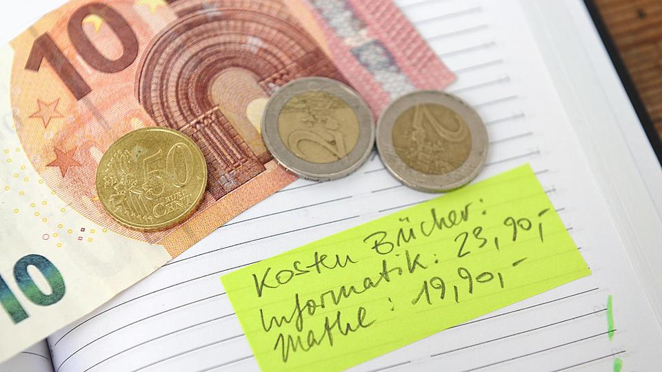 Nahaufnahme eines aufgeschlagenen linierten Buches auf dem ein Geldschein und drei Münzen liegen.