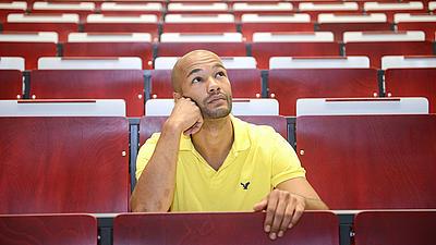 Ein junger Mann sitzt allein in einem Hörsaal in einer der vorderen Reihen, seinen Kopf hat er mit seiner rechten Hand abgestützt, er blickt nachdenklich nach oben.