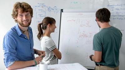 Drei Menschen stehen vor einen Flipchart und besprechen sich.