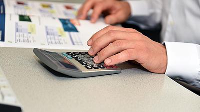 Ein Mitarbeiter im Vertrieb prüft Preise mit einem Taschenrechner.