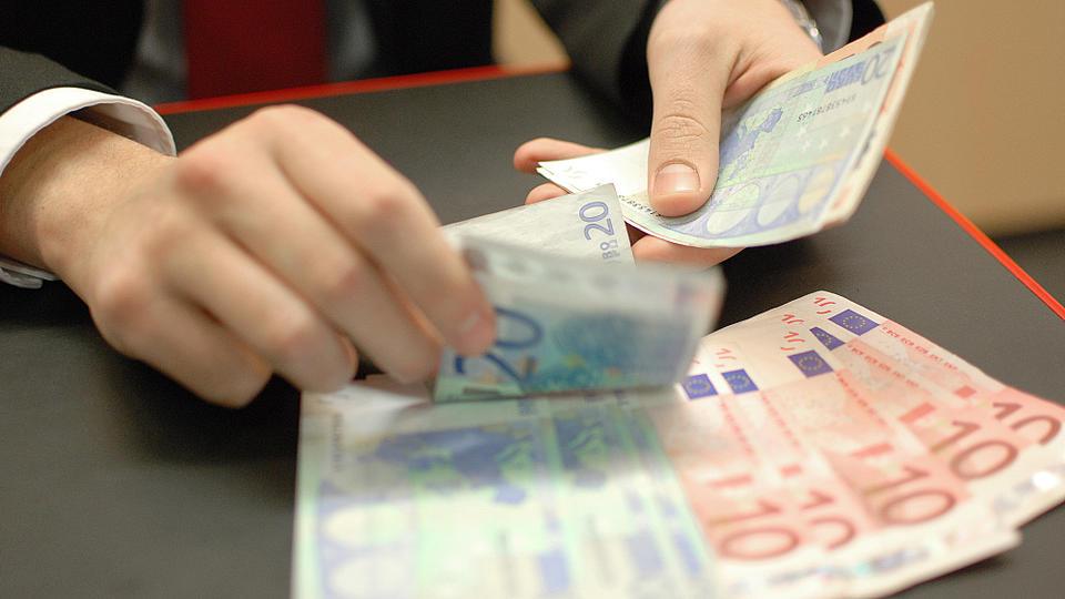Zwei Hände zählen Geldscheine ab.