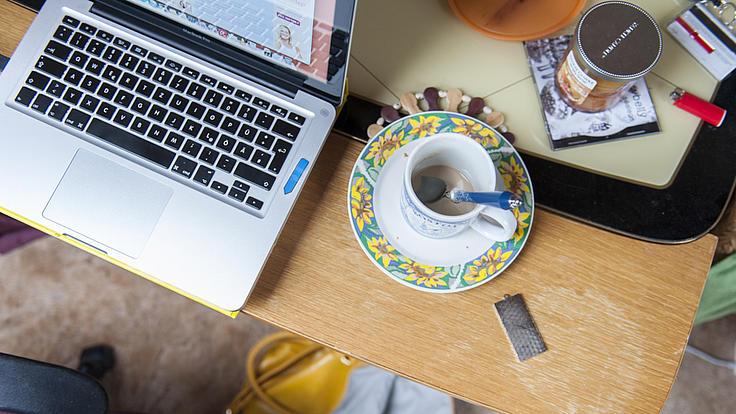 Laptop und Kaffeetasse auf einem Schreibtisch.