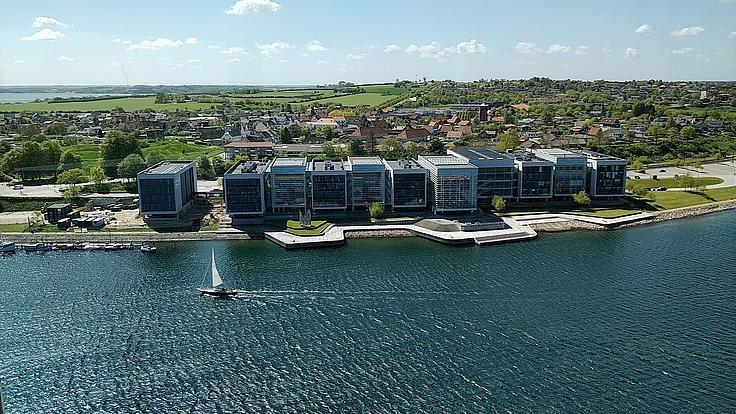 Der Campus in Sonderborg von oben. Vorne Wasser und ein kleines Segelboot. Im Hintergrund der Campus mit Glasfassaden.