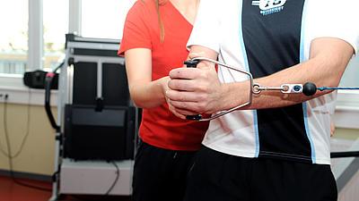 Eine Phyiotherapeutin hilft einem Patienten.
