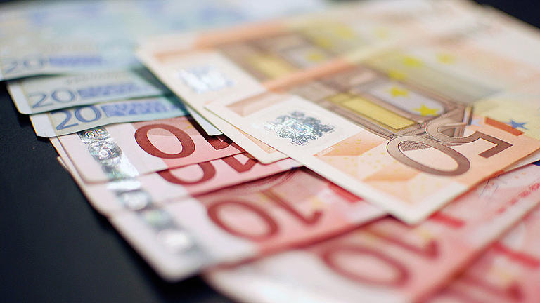 More money (210,00 Euros) laying on a desk.