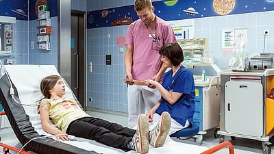 In einer Notaufnahme liegt ein Mädchen. Ein Mann und eine Frau kümmern sich um sie.