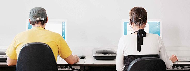 Zwei Studierenden sitzen an Bildschirmen.
