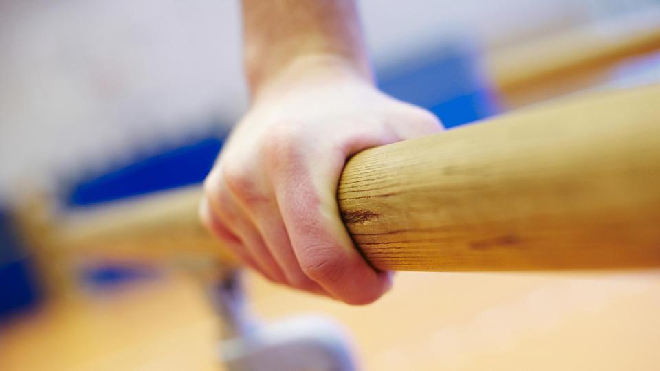 Nahaufnahme einer Barrenstange auf die sich eine Hand stützt