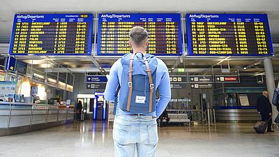 Aufnahme eines jungen Mannes von hinten in einer Abflughalle.