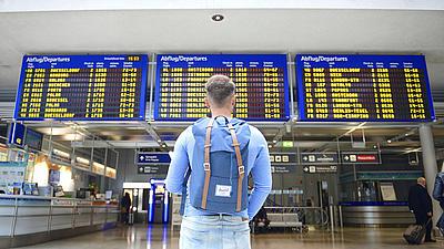 Aufnahme eines jungen Mannes von hinten, er hat kurze Haare, ist bekleidet mit einer blauen Jeans, einem blauen Langarmshirt, hat einen blauen Rucksack auf dem Rücken und steht vor den Anzeigetafeln einer Abflughalle in einem Flughafen.