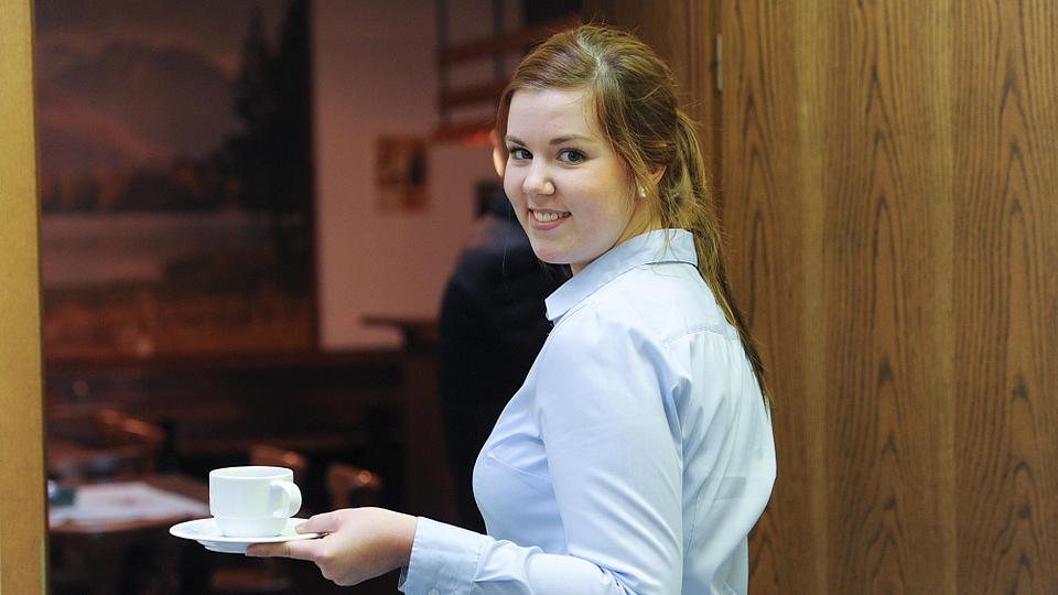 Eine Kellnerin bringt eine Tasse Kaffee.