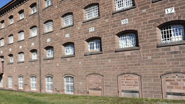 Hinter einem Grünstreifen steht ein gemauertes Gebäude mit weißen Gittern vor den Fenstern. Am Gebäude sind Zahlen aufgemalt.
