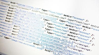 Nahaufnahme von einem Programmiercode, dargestellt auf einem Computermonitor. Zu sehen ist schwarze und blaue Schrift auf weißem Hintergrund.