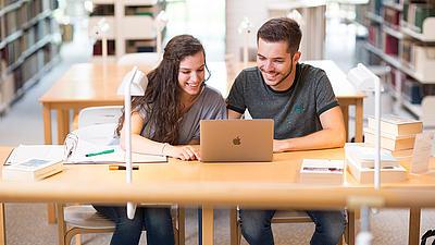 Zwei Studierende lernen gemeinsam in einer Bibliothek.