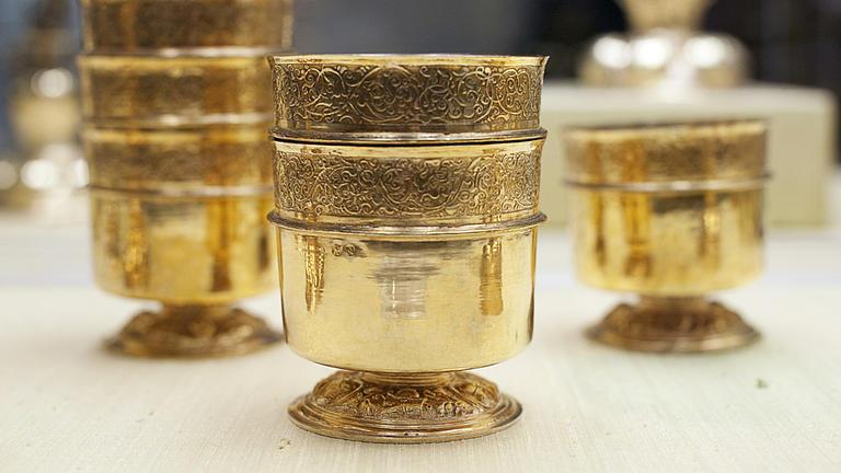 Verschiedene Goldene Kelche in unterschiedlichen Größen stehen auf einer hellen Fläche.