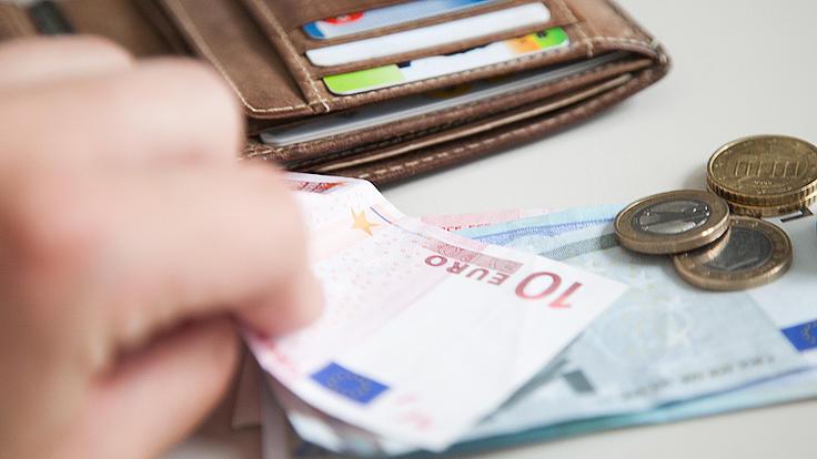 Eine Hand holt Geld aus einem Geldbeutel.