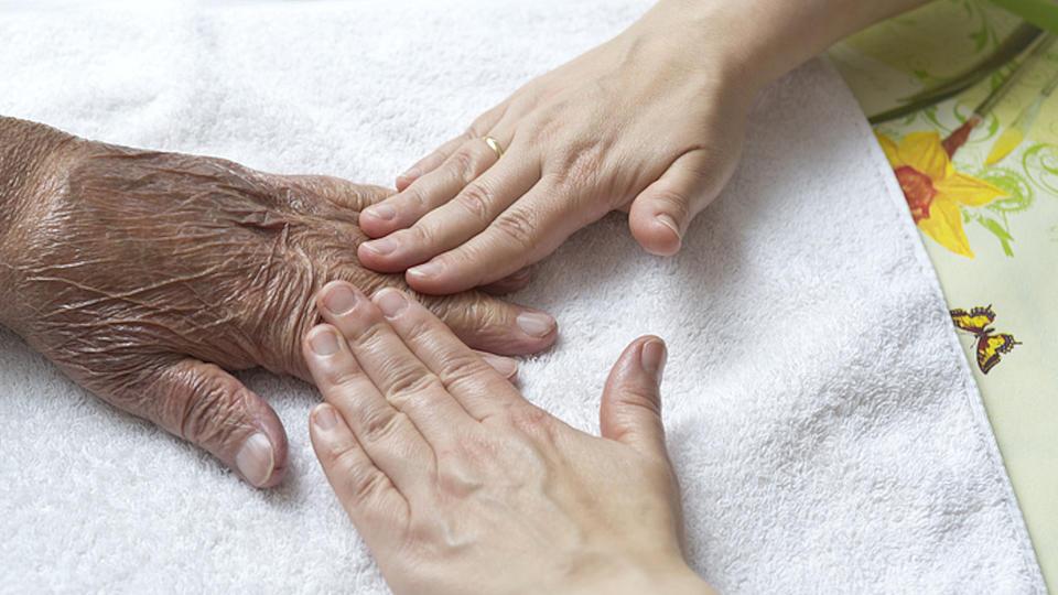 Junge Hände streichen über die Hand einer älteren Person