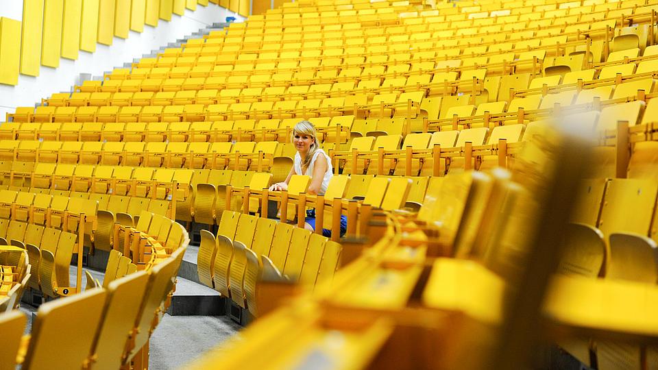Eine blonde Frau sitz alleine in einem großen Vorlesungssaal mit gelben Stühlen.
