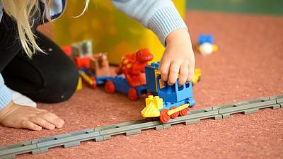 Ein Mädchen spielt mit einer Eisenbahn.