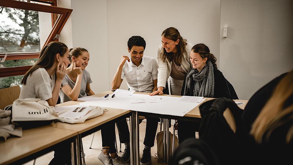Studenten sitzend an einem Tisch und sprechend über einen Plan, der vor ihnen auf dem Tisch liegt