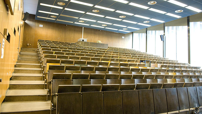 Blick in einen leeren Hörsaal, dessen Sitzreihen aus Holz bestehen. Auch die Wandverkleidung ist holzfarben. An der einen Seite lässt eine riesige Fensterfront Licht herein.