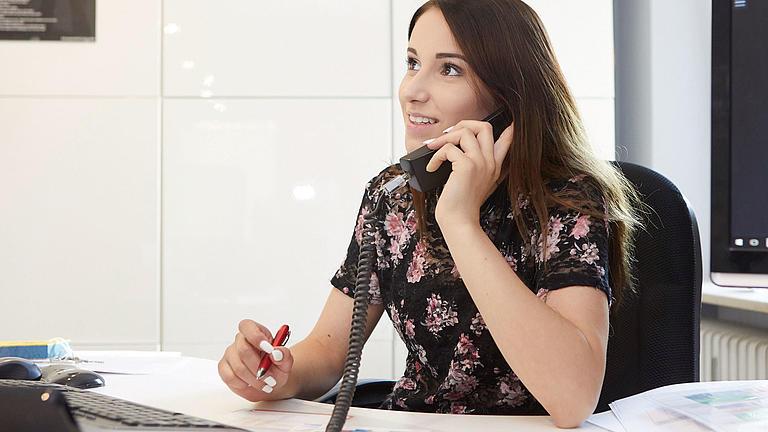 Ein junge Frau sitzt an einem Schreibtisch mit Computer, telefoniert und hat einen Stift in der Hand.