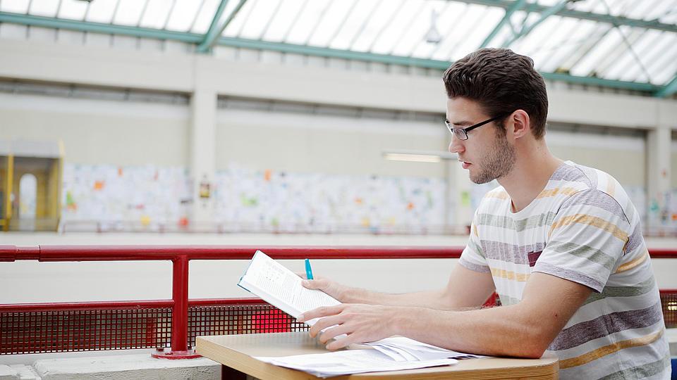 Ein Student sitzt in der Uni und lernt.