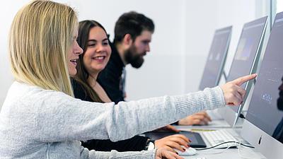 Studenten sitzend vor dem PC. Eine Studentin zeigt mit dem Finger auf den Bildschirm.