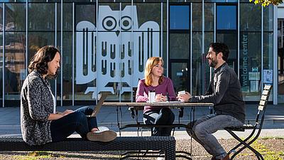 Studierende unterhalten sich vor dem Unigebäude im Sonnenschein