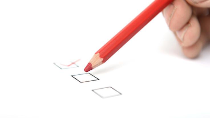 Eine Checkliste mit drei schwarzen quadratischen Kästchen von denen das obere mit einem roten Buntstift angehakt wurde.