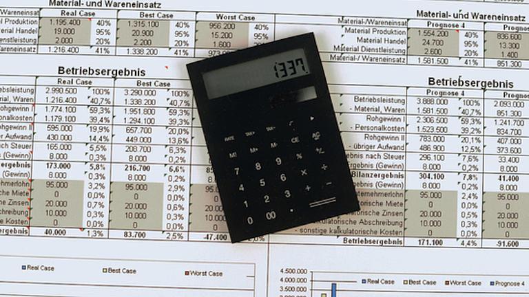 Auf einer ausgedruckten Statistik liegt ein schwarzer Taschenrechner dessen Display die Zahl 1337 zeigt.