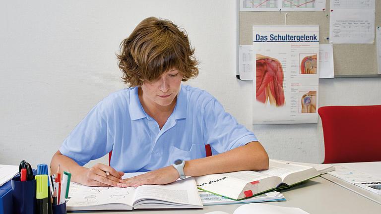 Eine Frau lernt in einem medizinischen Fachbuch.
