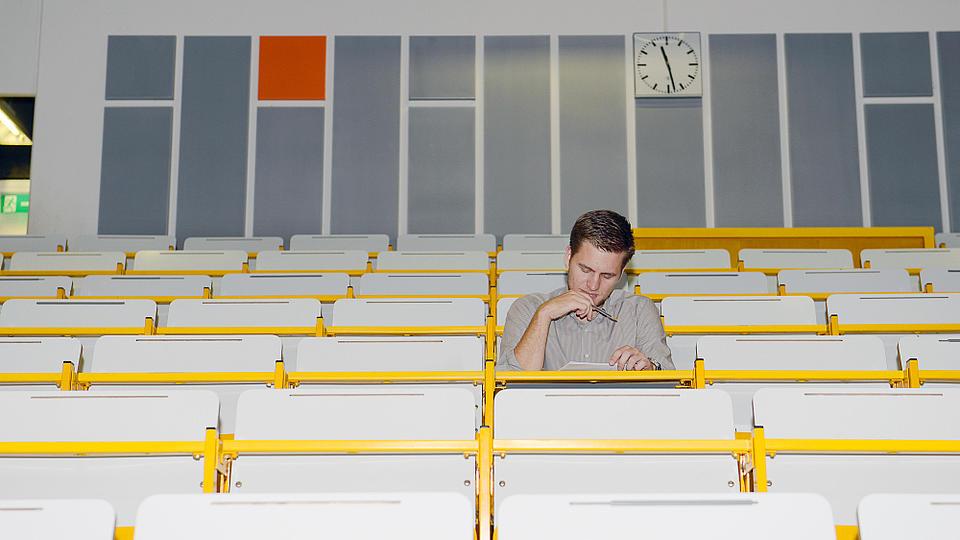 Ein junger Mann sitzt in einem Vorlesungssaal.