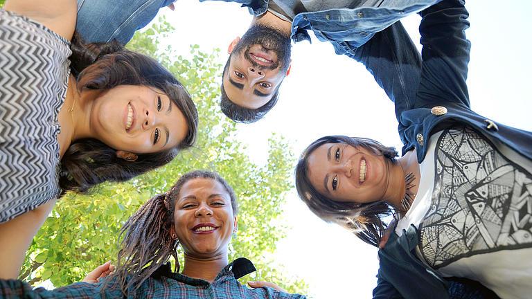 Vier junge Menschen schauen von oben in eine Kamera.
