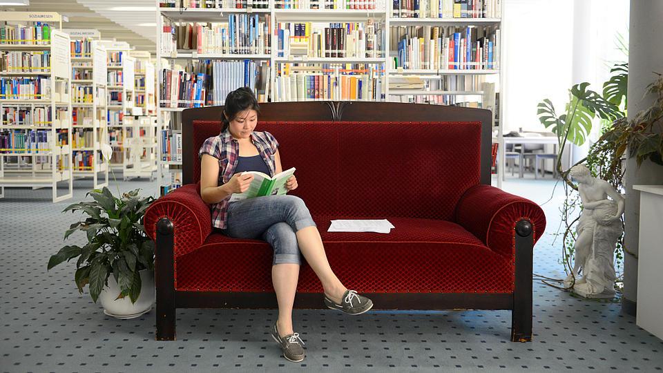 Eine junge Frau sitzt in einer Bibliothek auf einem roten Sofa und liest in einem Buch.