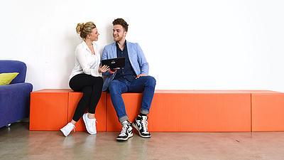 Eine junge Frau und ein junger Mann sitzen zusammen auf einem orangefarbenen Kasten neben einer blauen Couch.