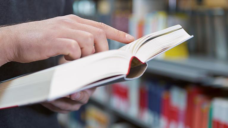 Ein Studierender liest in einem Buch.