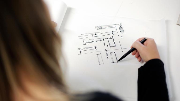 Eine Frau skizziert auf den vor ihr liegenden Zeichenblock mit einem schwarzen Stift Vierecke und Linien.