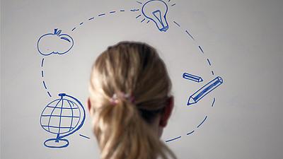 Eine Frau schaut auf eine weiße Tafel mit blau gezeichneten Symbolen.