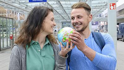 Eine junge Frau mit grauen Strickjacke und ein junger Mann mit Rucksack stehen unter dem überdachten Bereich vor einem Flughafenterminal.