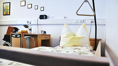Ein Krankenbett aufgenommen vom unteren Ende. Neben dem Krankenbett steht ein Nachtschrank mit ausklappbarem Tablett. An der Wand hängen Bilder in verschiedenen Größen.