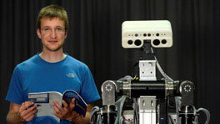 Ein Mann und ein Roboter stehen nebeneinander.