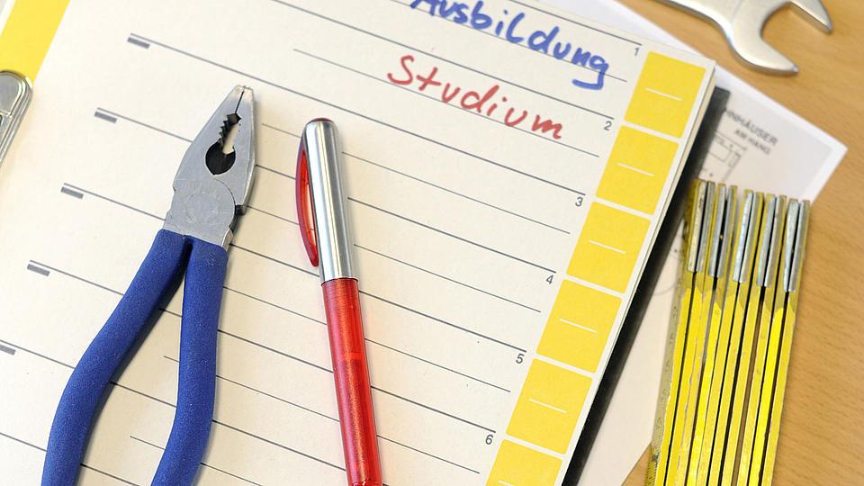 Werkzeug und Kugelschreiber liegen auf einem Ordner mit Lernmaterial.