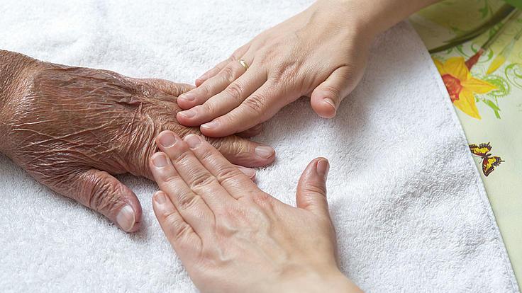 Drei Hände auf einem Handtuch.