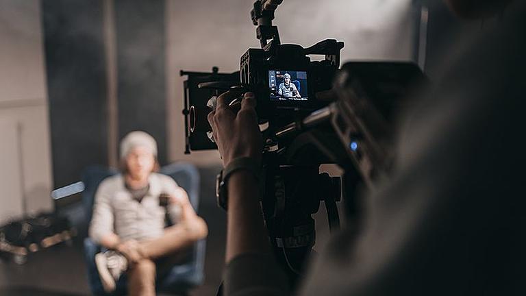 Ein Student wird interviewt und dabei mit einer professionellen Kamera gefilmt.