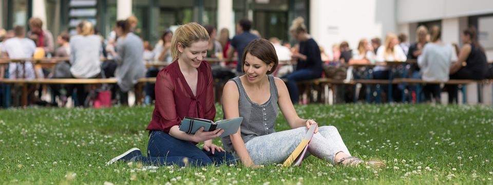 Zwei Studierende sitzen gemeinsam auf einer Wiese.