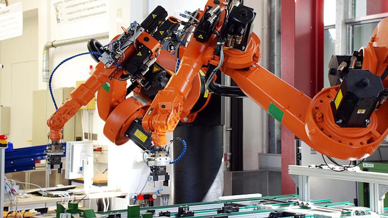 Ein oranger Roboterarm steht  in einer Werkhalle über einem Produktionstisch, auf dem verschiedene Metallteile liegen.
