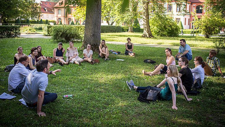 Studierende sitzen gemeinsam auf einer Wiese.
